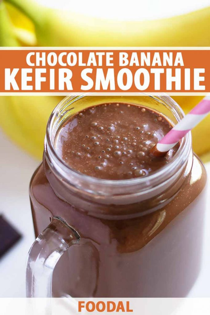 Vertical image of a glass jar with a handle filled with a dark brown smoothie and a straw, with bananas in the background and text on the top and bottom of the image.