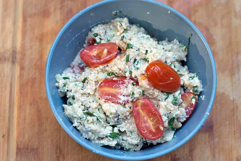 Horizontal image of a ricotta, cauliflower, herb, and tomato mixture.