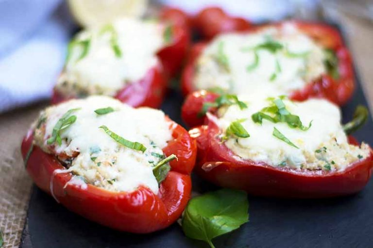 Horizontal image of stuffed red vegetables with cheese on a slate.