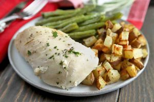 Horizontal image of a slow cooked herb chicken breast on a plate with portions of green beans and roasted potatoes, on a brown wood table with red cloth napkins and silverware in the background.