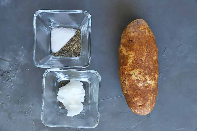 Horizontal image of a whole potato, salt, pepper, and coconut oil in bowls.