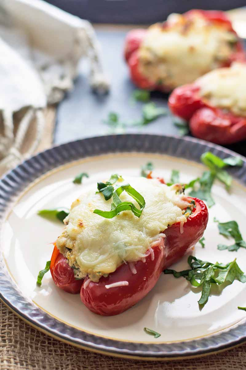 Vertical image of plates with halved red vegetables filled with cheese and riced cauliflower with fresh herbs.