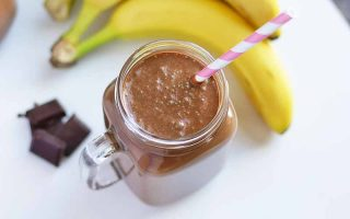 Horizontal image of a glass mug with a cacao smoothie and straw next to whole bananas and chocolate pieces.