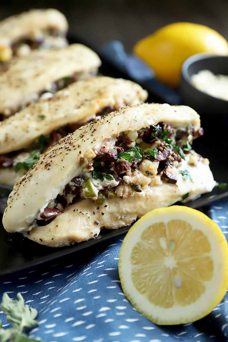 Vertical image of a row of cooked chicken breasts slit in half with a mixture on a black tray next to a blue towel and lemon half.