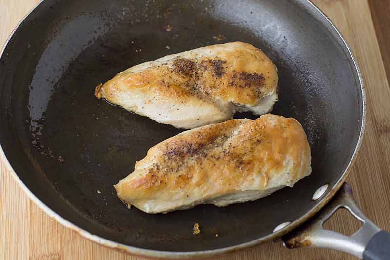 Horizontal image of a skillet with seared chicken breasts.