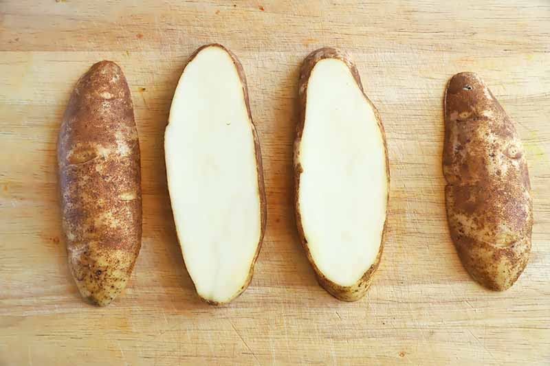 Horizontal image of four slices of a whole potato on a wooden cutting board.