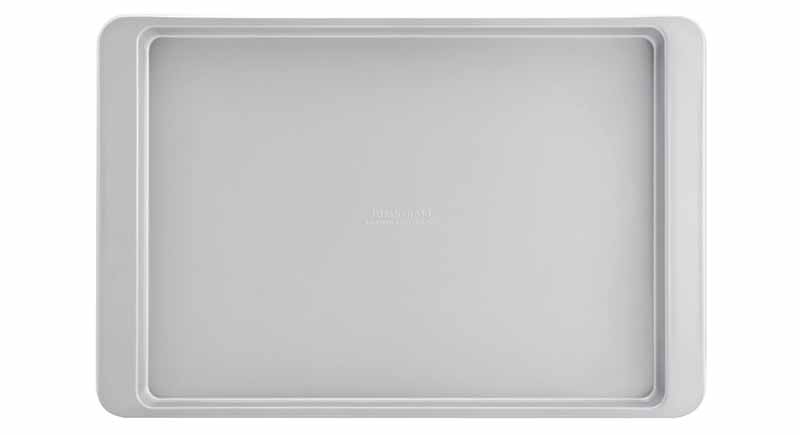Overhead image of rimmed silver-colored aluminum baking sheet with raised rim around all four sides, isolated on white background.