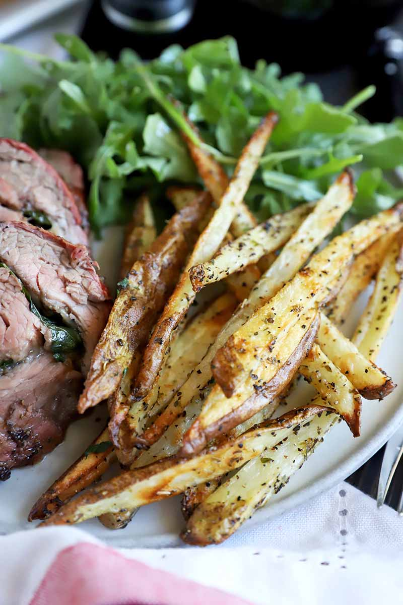 Vertical image of a pile of skinny seasoned french fries next to steak and salad on a plate.
