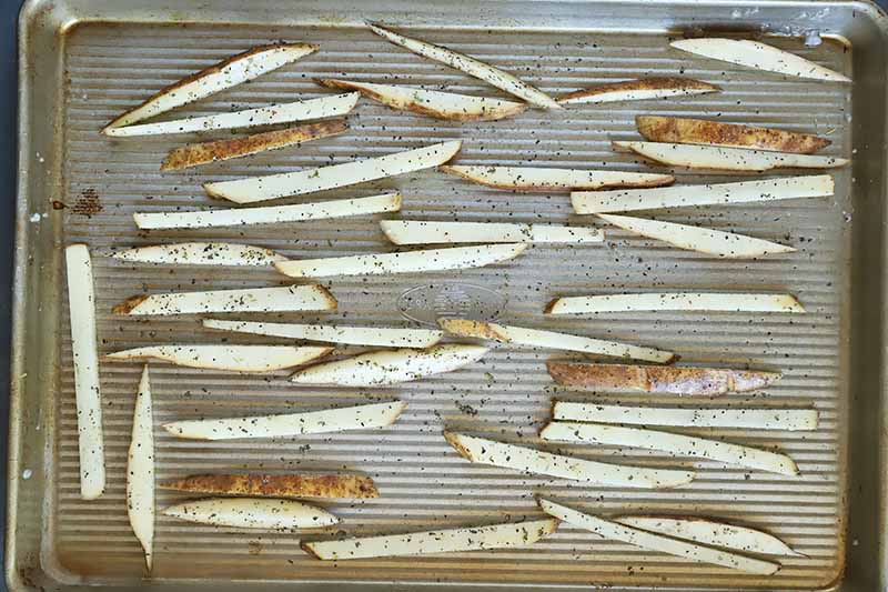 Horizontal image of raw potato matchsticks with seasonings scattered on a baking sheet.