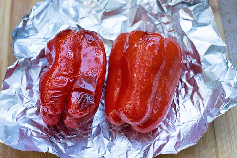 Horizontal image of two whole roasted red peppers on foil.