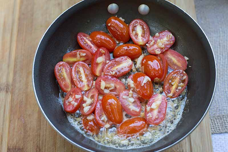 Horizontal image of cooking sliced grape tomatoes in a pan.