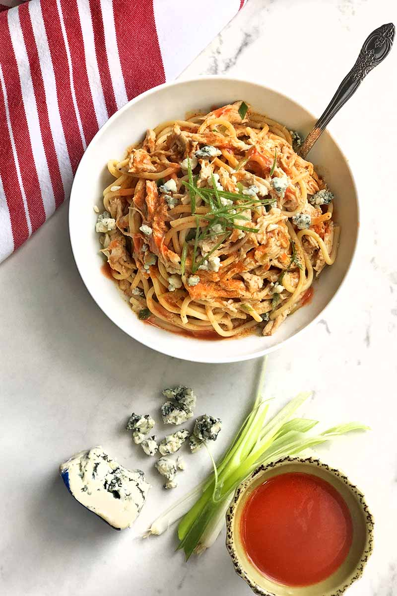 Vertical overhead image of a white bowl of Buffalo chicken spaghetti garnished with chopped scallions with a fork stuck in it, with a red and white striped cloth napkin, blue cheese, whole green onions, and a small dish of hot sauce, on a white and gray background.