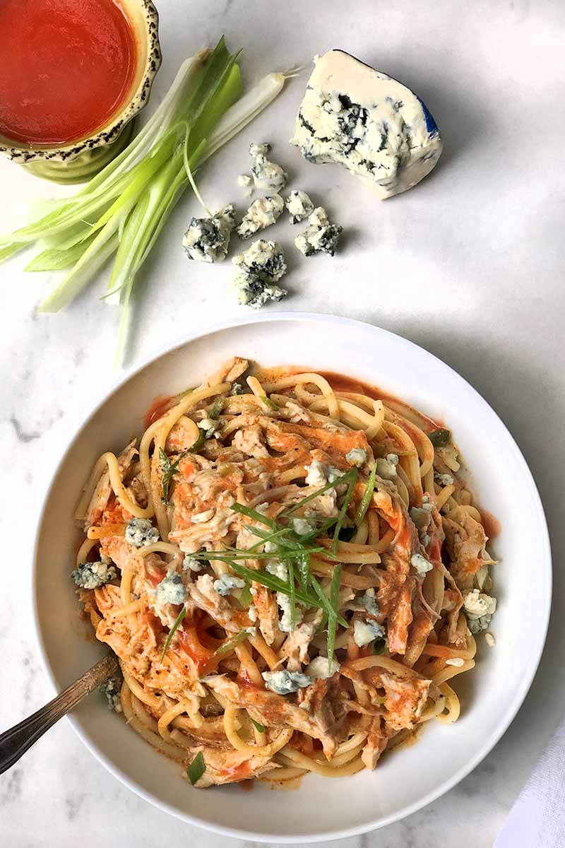 Vertical overhead image of spaghetti with shredded cooked poultry, Buffalo sauce, blue cheese, and scallions, with a fork stuck into the bowl, on a gray and white background with crumbled gorgonzola, whole green onions, and a small bowl of red hot sauce.