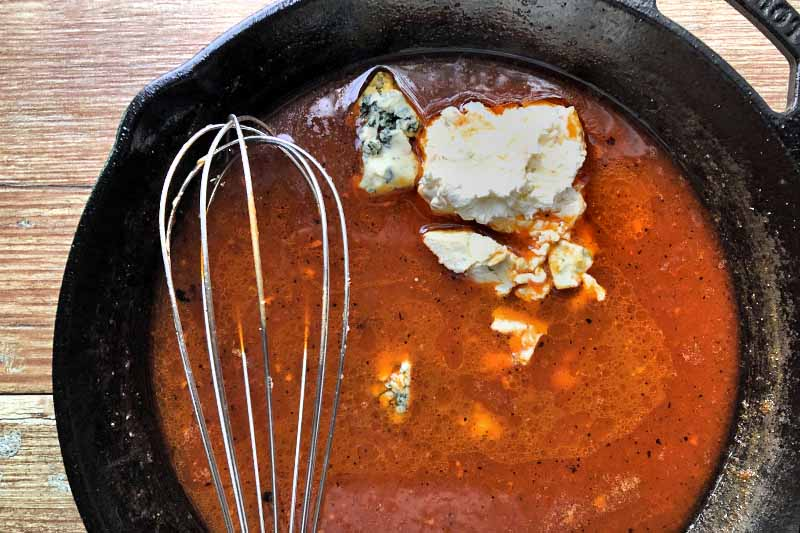 Overhead closely cropped horizontal image of a large cast iron pan of hot sauce with a whisk stirring gorgonzola and cream cheese into the mixture, on a brown surface.