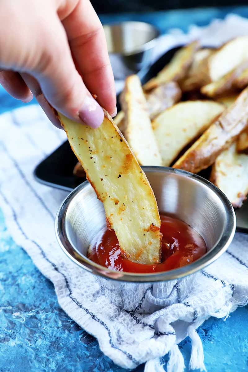 Vertical image of a hand dipping a wedge of potato in a metal bowl filled with ketchup on top of a white towel on a blue surface.