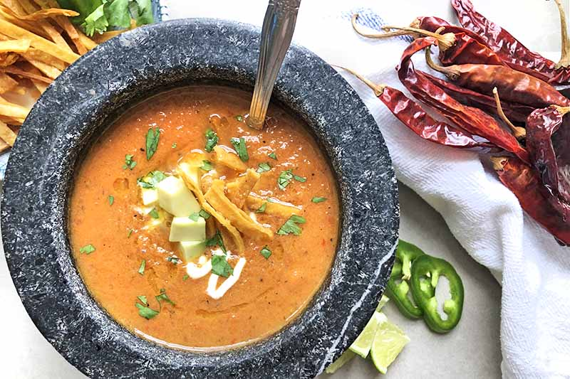 Horizontal overhead image of a bowl of Mexican tortilla soup to the left, with various garnishes and red chili peppers on a white cloth napkin to the right, on a gray surface.