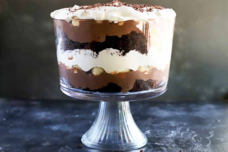 Horizontal image of a large glass serving dish with a layered dessert of pudding, whipped cream, chocolate cake, and banana slices.
