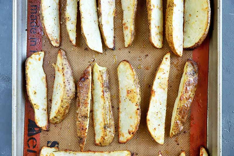 Horizontal image of baked wedges of spuds on a baking sheet lined with a silicone mat.