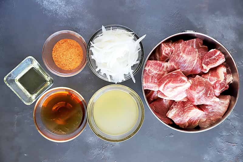 Horizontal image of cubed uncooked meat, sliced onions, and assorted seasonings in bowls.
