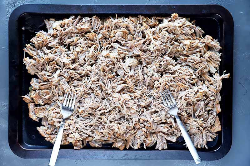 Horizontal image of a baking sheet with shredded cooked pork and two metal spoons.