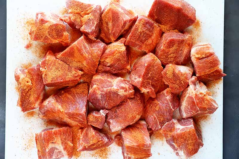 Horizontal image of raw seasoned pork cubes.