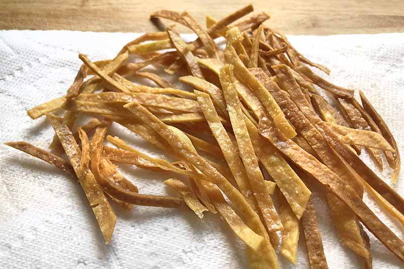 Horizontal image of fried tortilla strips draining on a paper towel, on a wood surface.