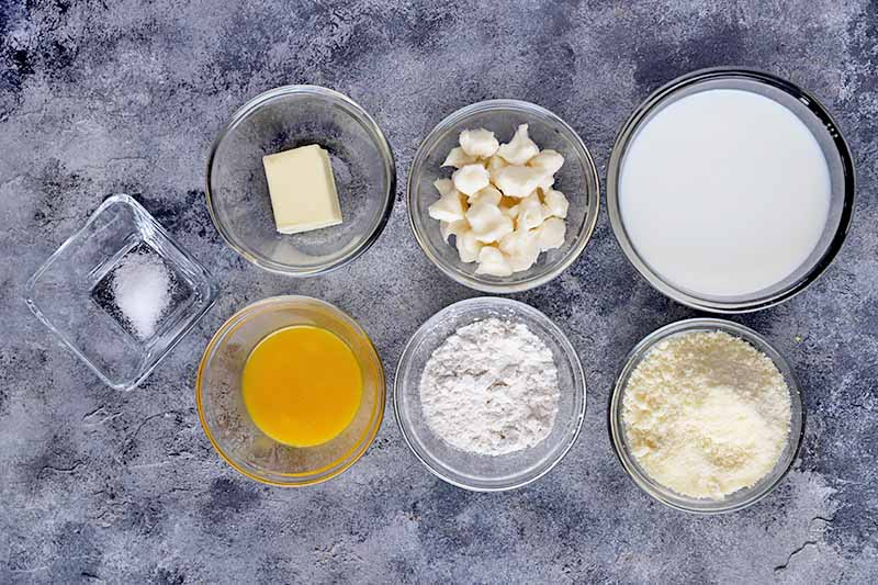 Horizontal image of ingredients in bowls to make a mornay sauce.