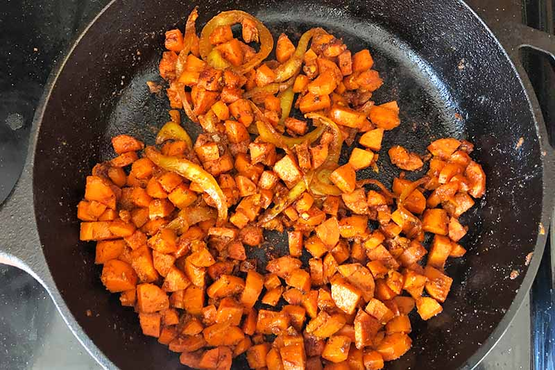 Horizontal image of cooking diced carrots and sliced onions with spices in a pan.