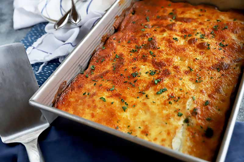 Horizontal image of a whole baked and browned moussaka topped with finely chopped herbs.
