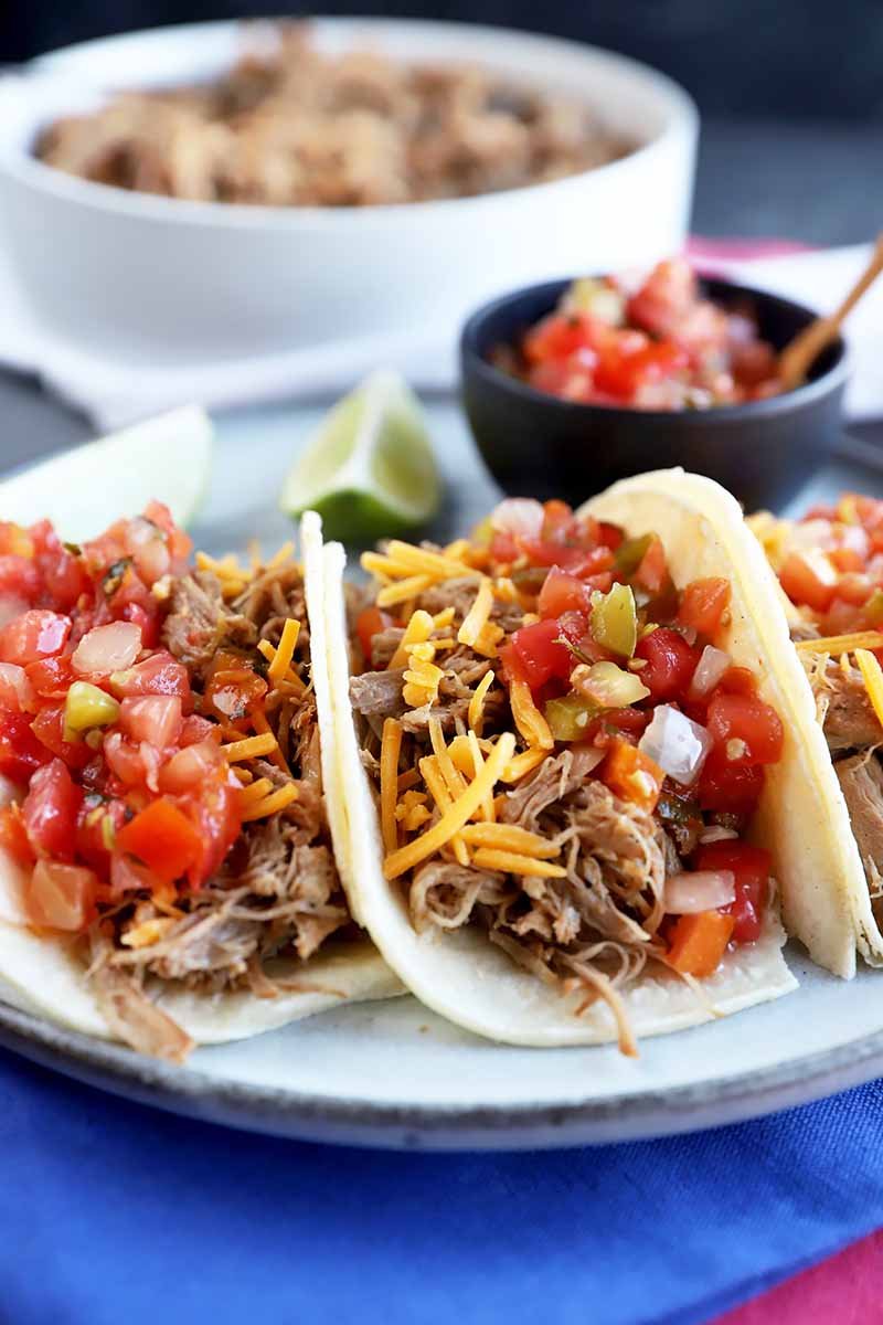 Vertical image of tacos filled with meat and topped with cheese and tomato garnishes.