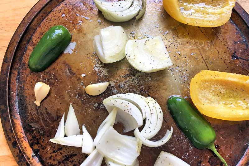 Overhead horizontal image of chopped onion, garlic, jalapenos, and yellow bell pepper on a round metal baking pan, on a wood surface.