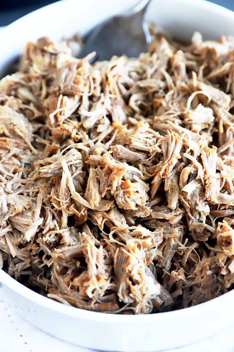 Vertical close-up image of flaked pork meat.