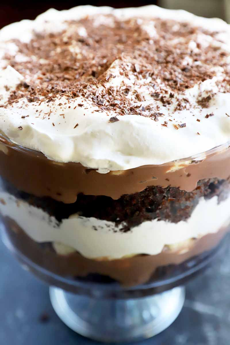 Vertical close-up image of a layered trifle in a glass dish.