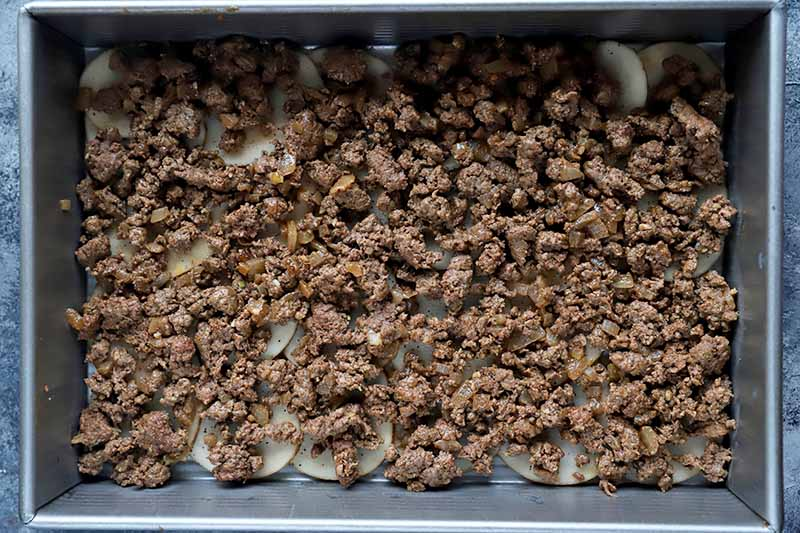 Horizontal image of a layer of ground meat over sliced potatoes in a baking dish.