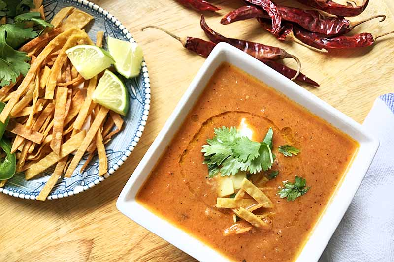 Horizontal overhead image of a square white bowl of soup garnished with fried tortilla strips, cilantro, avocado, and sour cream, with a plate of additional garnishes including lime wedges and a white cloth napkin, on a wood surface with a pile of dried red chili peppers.