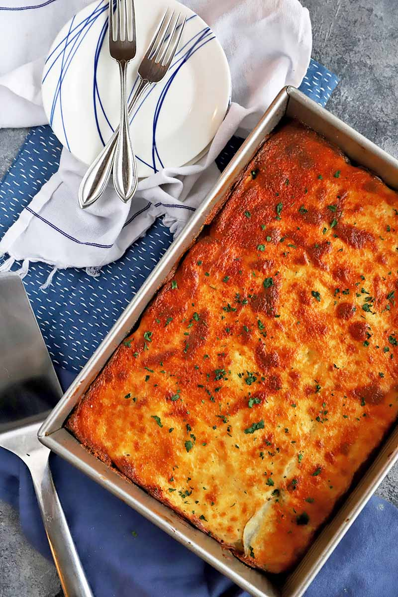 Vertical top-down image of a whole baked, browned casserole garnished with fresh herbs in a rectangular baking dish next to plates, forks, a serving knife, and a towel.