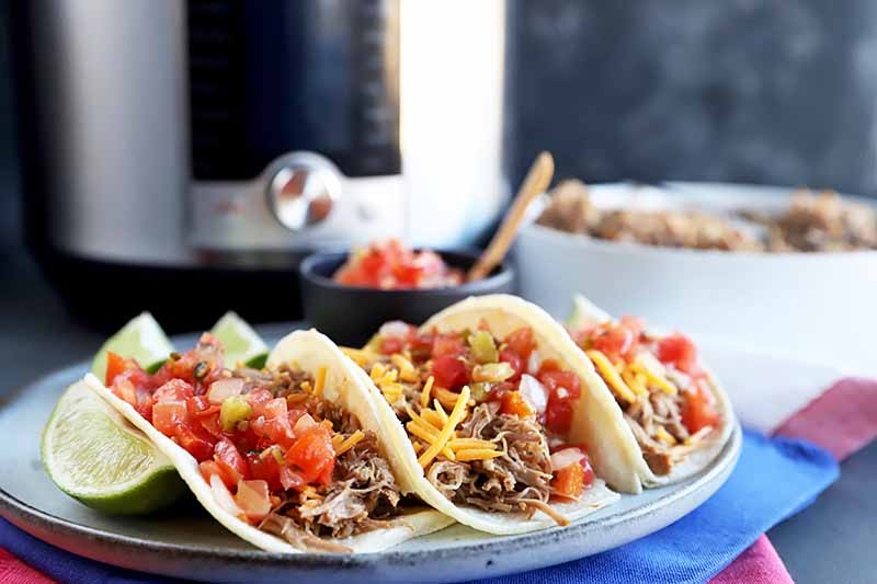 Horizontal image of three meat tacos garnished with tomatoes and cheese in front of a kitchen appliance and a white bowl of cooked meat.