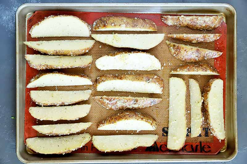 Horizontal image of neatly arranged wedges of uncooked potatoes on a baking sheet with a silicone mat.