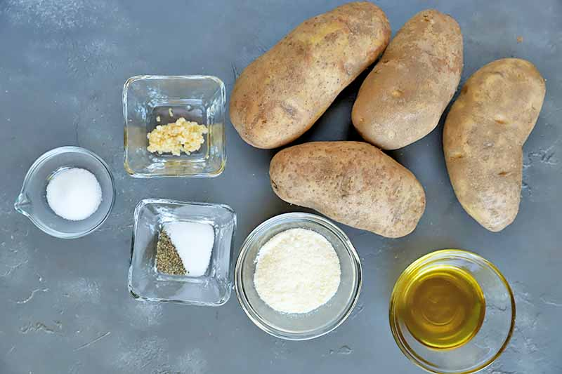 Horizontal image of four whole spuds and a variety of other ingredients and seasonings in glass dishes on a gray surface.