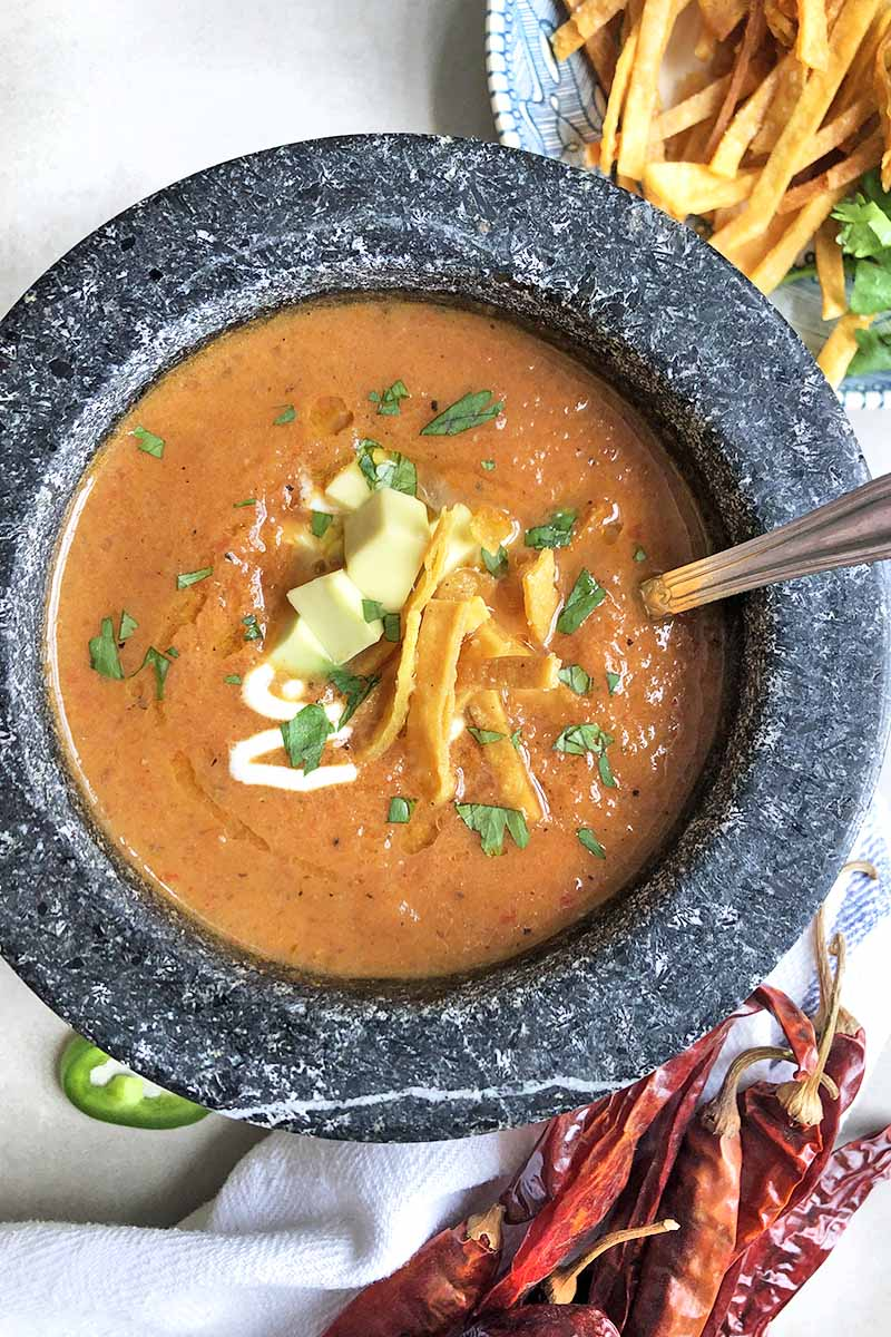 Vertical overhead image of a gray bowl of Mexican tortilla soup with avocado, crema, and cilantro for garnish, on a gray surface with a white cloth napkin, dried red chilies, and a plateful of additional garnishes.