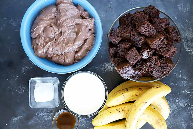 Horizontal image of cocoa cake chunks, whole bananas, liquids, seasonings, and pudding in various dishes.