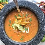 Horizontal overhead image of a gray ceramic bowl of vegetarian soup with a spoon, garnished with fried tortilla chips, chopped cilantro, sour cream, and avocado, on a gray surface with more garnishes scattered around and on a plate at the top left, with dried red chilies de arbol on a folded white cloth napkin to the right.