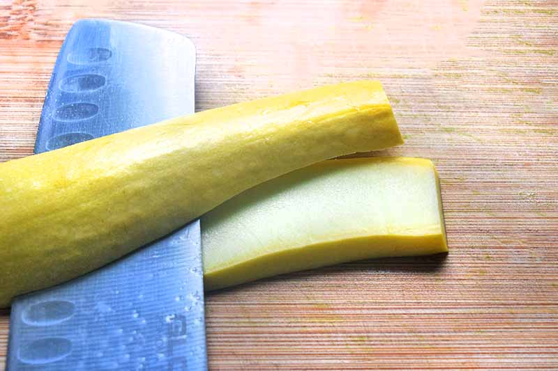 Horizontal overhead image of a knife slicing a yellow squash into slabs, on a wood cutting board.