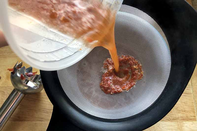 Horizontal overhead image of a hand pouring a plastic container of pepper puree into a plastic strainer below, with an immersion blender on a wood surface.