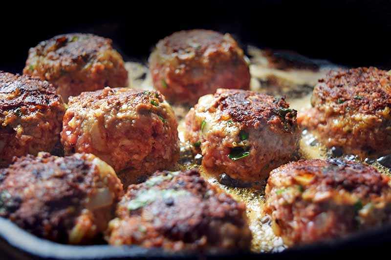 Closeup horizontal image of nine meatballs browning in a frying pan.