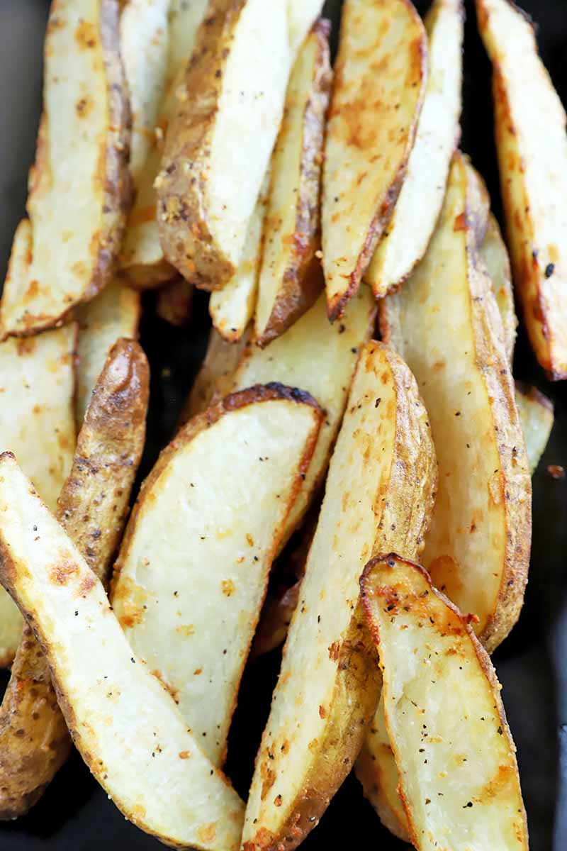 Vertical close-up image of baked and seasoned potato fries.