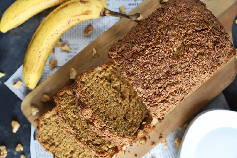 Horizontal image of a baked loaf topped with streusel with slices on a wooden board next to bananas and walnuts.