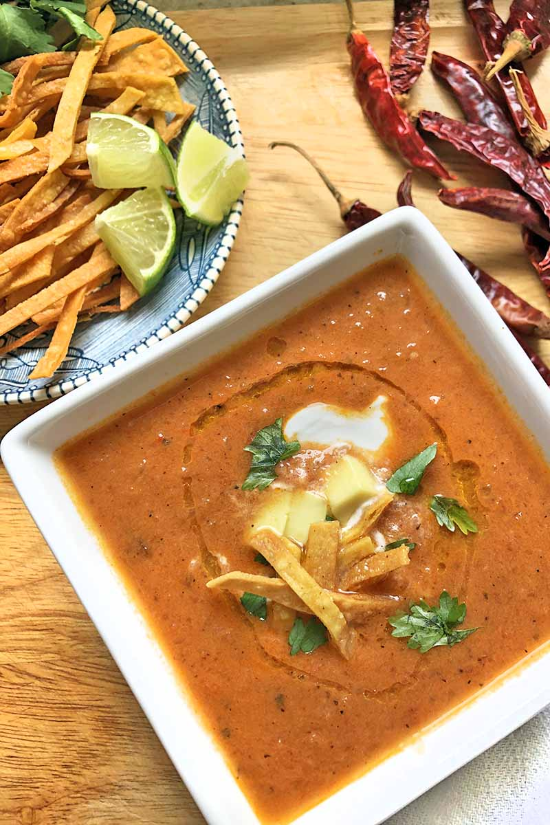 Vertical overhead image of a square bowl of homemade soup topped with fried tortilla strips, sour cream, and chopped cilantro, on a wood surface with a small plate of more garnishes including lime wedges and fresh herbs, with dried chilies de arbol scattered at the top left of the frame.