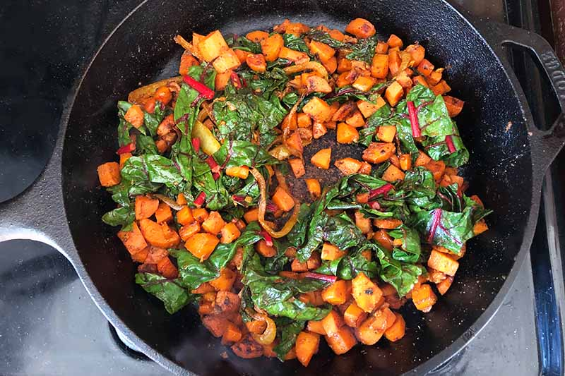 Horizontal image of cooking diced carrots, sliced onions, and greens in a pan.