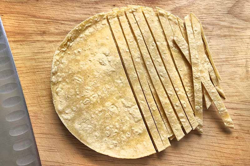 Overhead horizontal image of a stack of tortillas, half of which have been sliced into strips, on a wooden cutting board with a knife to the left.